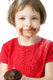 Beautiful Four Year Old with Chocolate Muffin. Beautiful four year old girl covered in flour and chocolate, holding chocolate chip muffin. Shot in studio over Royalty Free Stock Photo