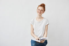 Beautiful foxy female student smiling holding notebook. Stock Photo