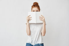 Beautiful foxy girl hiding face behind book looking at camera. Royalty Free Stock Image