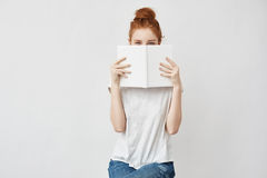 Beautiful foxy girl hiding face behind book looking at camera. Royalty Free Stock Photos