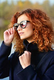 Beautiful foxy hair. Autumn style. Beautiful young woman with bright foxy hair wearing sunglasses and black coat. Beauty, fashion Stock Photo