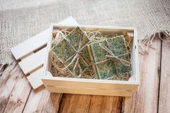 Beautiful, fragrant handmade soap in wooden box standing on a wooden and burlap background stock photos