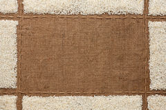 Beautiful frame with rice  on sackcloth Stock Photography