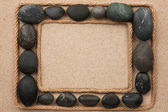 Beautiful frame with rope and black stones on sand Royalty Free Stock Image