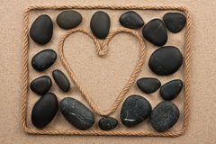 Beautiful frame of rope in the form of heart with black stones Royalty Free Stock Photo