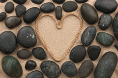 Beautiful frame of rope in the form of heart with black stones Royalty Free Stock Photography