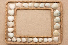 Beautiful frame with rope and sea shells on sand Stock Photo
