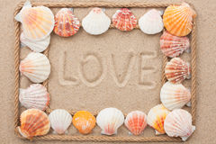 Beautiful frame of rope and seashells on the sand with text love Stock Photos