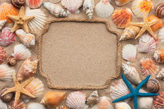 Beautiful frame of rope, seashells and starfish on the sand, with place for your text Royalty Free Stock Images