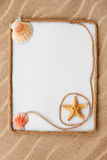 Beautiful frame of rope and star and sea shells with a white background on the sand Royalty Free Stock Photos