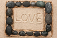 Beautiful frame of rope and stones on the sand with text love Stock Photo