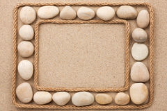 Beautiful frame with rope and white stones on sand. As a background stock images
