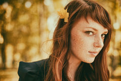 Beautiful freckle woman with red hair in fall park. Beautiful freckle woman with red long hair in fall park Stock Photography
