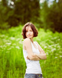 Beautiful freckled young woman with folded arms in summer day Stock Image