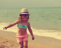 Beautiful free kid girl walking in the beach. Instagram effect portrait. Beautiful free kid girl walking in the beach on sea background. Instagram effect Royalty Free Stock Photography
