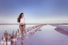 Beautiful free sexy girl in white swimwear posing on salty beach Stock Photos