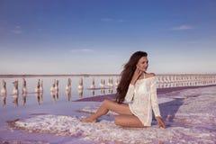 Beautiful free sexy girl in white swimwear posing on salty beach Stock Photo