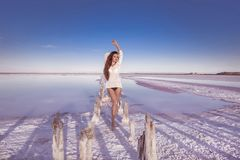 Beautiful free sexy girl in white swimwear posing on salty beach Stock Photography