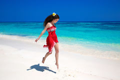 Beautiful free young woman jumping on the exotic sea, brunette s Royalty Free Stock Photo