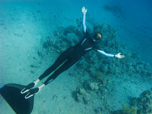 Beautiful freediver girl poses near the coral reef. And sand bottom of the Red Sea royalty free stock photo