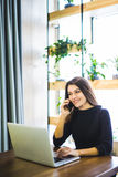 Beautiful freelancer female working on line and talking on the phone and browsing in a laptop at home or office. Freelancer female working on line and talking on Royalty Free Stock Photos