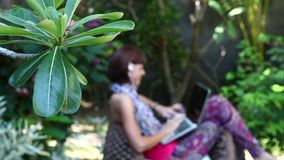Beautiful freelancer woman working on a computer at her villa with green tropical garden. Bali island, Indonesia. stock footage