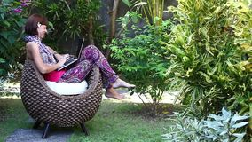 Beautiful freelancer woman working on a computer at her villa with green tropical garden. Bali island, Indonesia. Beautiful freelancer woman working on a stock video footage