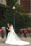 Beautiful french bride in long dress hugging in old street vines Stock Photography