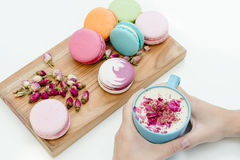 Beautiful french macarons on the desk. Woman hands holding blue cup of cappuccino with roses petals Royalty Free Stock Images