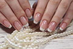 Beautiful French manicure. On a trendy background stock photography