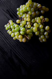 Beautiful fresh bunch of grapes on a dark wooden background. The droplets of water. Healthy eating Royalty Free Stock Image