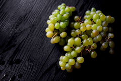 Beautiful fresh bunch of grapes on a dark wooden background. The droplets of water. Healthy eating Royalty Free Stock Images