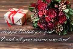 Beautiful fresh flower arrangement of red roses, gift box and text wish, birthday greeting card concept. stock photography