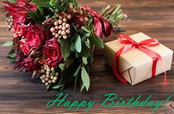 Beautiful fresh flower arrangement of red roses, gift box and text wish, birthday greeting card concept. royalty free stock photo