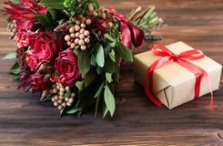 Beautiful fresh flower arrangement of red roses and gift box. royalty free stock photography