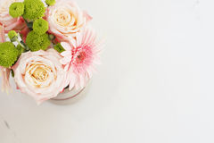 Beautiful fresh flowers on light marble table, top view. Pink roses and gerberas on a female work desk. Blogger lifestyle Stock Photography