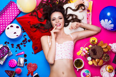 Beautiful fresh girl doll lying on bright backgrounds surrounded by sweets, cosmetics and gifts. Fashion beauty style. royalty free stock photos