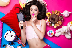 Beautiful fresh girl doll lying on bright backgrounds surrounded by sweets, cosmetics and gifts. Fashion beauty style. Photos shot in the studio royalty free stock photography