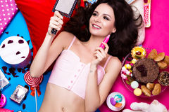 Beautiful fresh girl doll lying on bright backgrounds surrounded by sweets, cosmetics and gifts. Fashion beauty style. Stock Photography