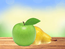 Beautiful fresh green apple and yellow pear on wooden table Royalty Free Stock Photography