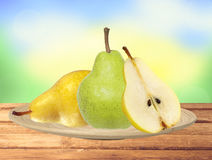 Beautiful fresh green and yellow pears on plate on table over na Stock Photo