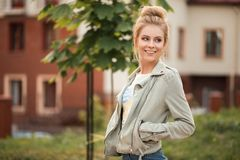 Beautiful fresh happy young woman with a smile. In a fashionable jacket walks in the city royalty free stock photo