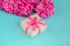 Beautiful fresh pink peony flower with gift box on mint background. Peonies summer.Mothers day or Womens day Stock Photo