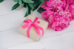 Beautiful fresh pink peony flower with gift box on wooden background. Peonies summer.Mothers day or Womens day Stock Image