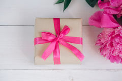Beautiful fresh pink peony flower with gift box on wooden background. Peonies summer.Mothers day or Womens day Royalty Free Stock Photography