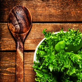 Beautiful Fresh Salad in a dish with wood spoon over vintage woo Stock Image