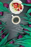 Beautiful fresh spring tulip with cup of coffee and cake on dark background. Coffee time. Flower gift. Beautiful fresh spring tulip with cup of coffee and fruit stock photos