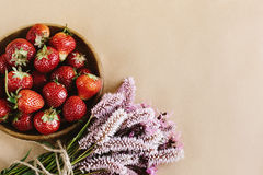 beautiful fresh strawberries and pink flowers on craft background, summer concept, space for your text royalty free stock images
