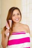 Beautiful fresh young girl wearing pink towel brushing her hair. Close up shot of beautiful fresh young brunette girl wearing pink towel brushing hair Stock Photo