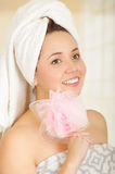Beautiful fresh young girl wearing towel holding pink loofah body sponge. Close up shot of beautiful fresh young brunette girl wearing towel holding pink loofah Stock Images
